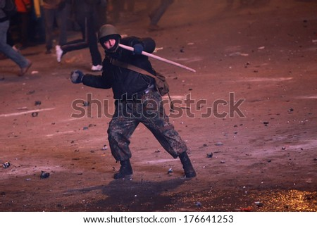 A protester throws a stone at police. Kyiv, Ukraine, January 19, 2014 - stock photo