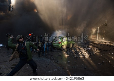 A protester throws a stone towards the pro-government forces during riots in Kiev, Ukraine, February 18, 2014 - stock photo