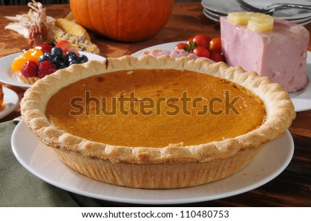 A pumpkin pie on a Thanksgiving dinner table - stock photo