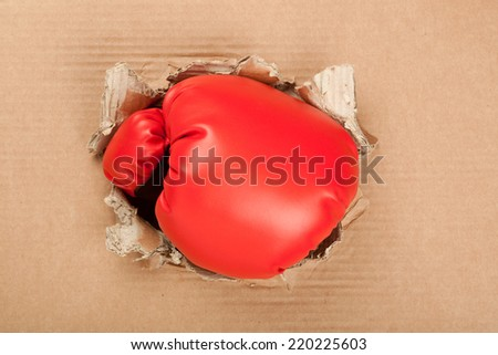 A punch breaking through an opening in a corrugated cardboard  - stock photo