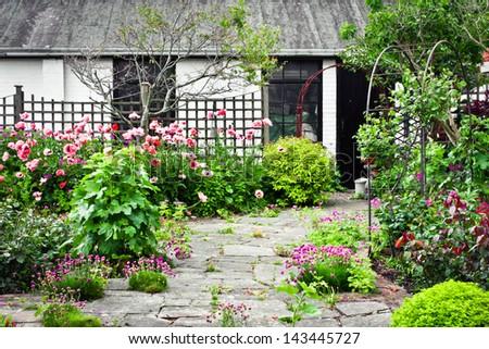 A quaint english country garden and patio - stock photo