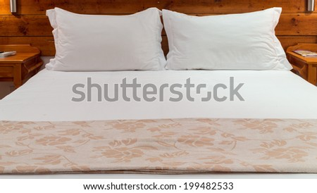 A queen sized bed with white bed sheets and two pillows - stock photo