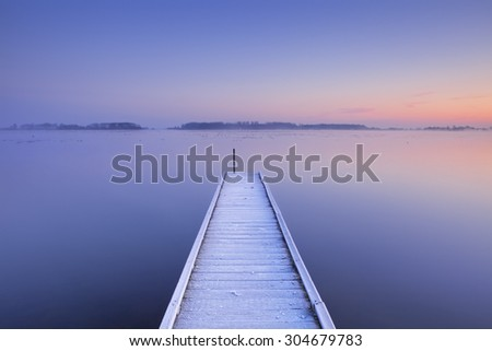 A quiet lake in The Netherlands with a jetty on an early winter morning. - stock photo