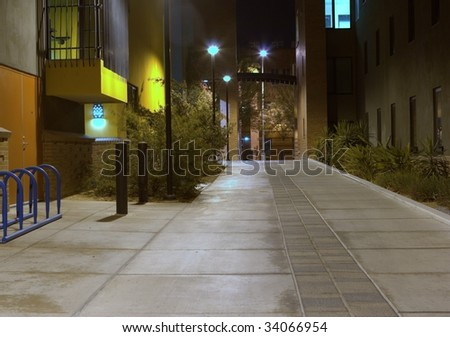 A quiet looking sidewalk between two buildings taken at night time - stock photo