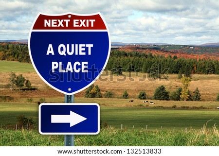 A quiet place Interstate road sign against a beautiful landscape - stock photo