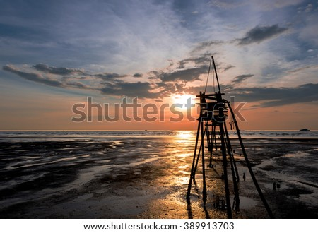 A quite and peaceful sunset by the beach overseen by a small pier - stock photo