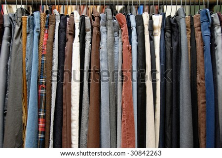 A rack of mens pants in a second hand shop - stock photo