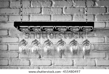 A rack of wine glasses hanging against brick wall. - stock photo