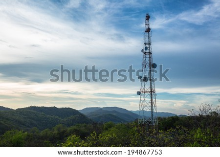 A radio communications tower at top of green mountain - stock photo