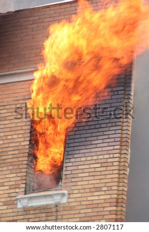A raging fire shooting from an apartment window - stock photo