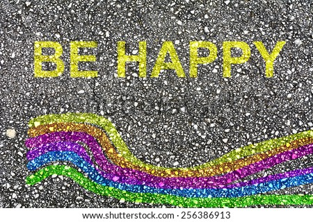 """A rainbow and the words """"be happy"""" painted on the pavement - stock photo"""