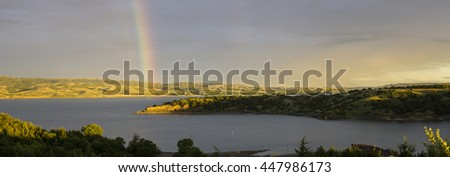 A rainbow at sunrise over the Missouri River at Platte, South Dakota.  Lake Francis Case. - stock photo