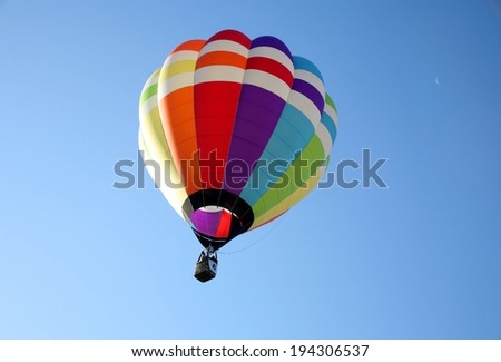 A rainbow colored hot air balloon in the sky. - stock photo