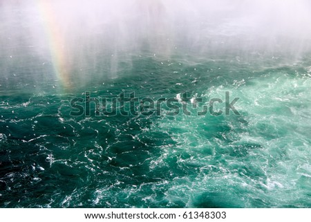 A rainbow emerging from rough and choppy water. - stock photo
