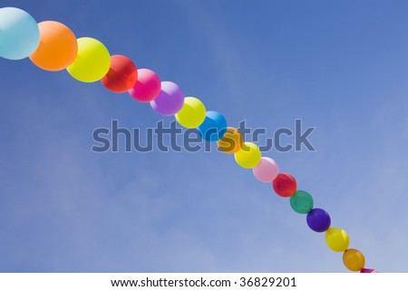 A rainbow made with coloured baloons in the sky - stock photo