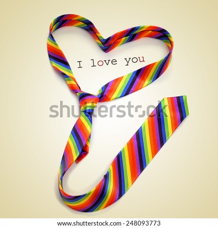 a rainbow necktie forming a heart and the text I love you written on a beige background, with a retro effect - stock photo