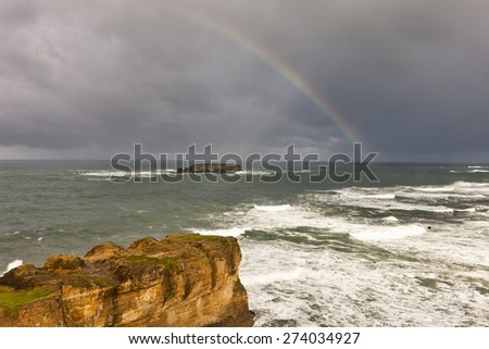 A rainbow over the Pacific Ocean as seen from Devil's Punchbowl north of Newport, Oregon. - stock photo