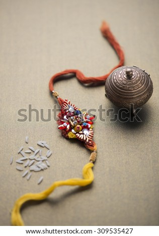 A Rakhi with rice grains and kumkum holder. An idian festive background. - stock photo