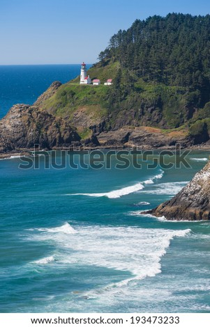 A rare bright sunny day at Heceta Head lighthouse on Oregon�¢??s central coast as brilliant white waves roll through a deep blue sea in the foreground. - stock photo