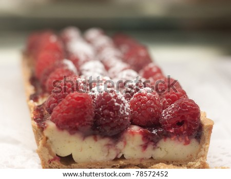A raspberry tart of custard and raspberries, sprinkled with powered sugar - stock photo