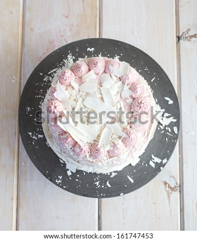 A raspberry white chocolate frosted cake from above. - stock photo