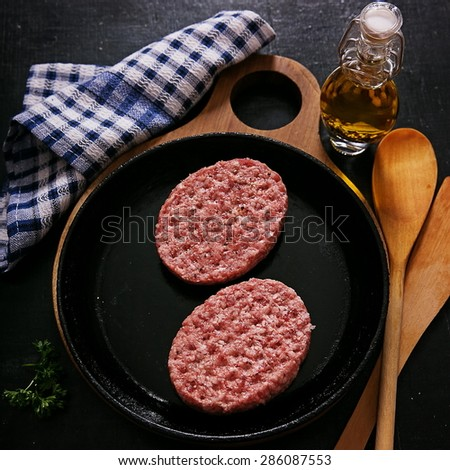 A raw cutlets on skillet before frying - stock photo