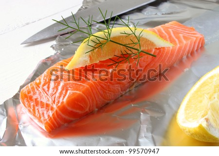 A raw fresh Salmon fillet, lemon slice and dill. - stock photo