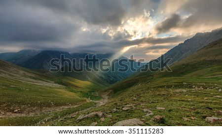 a ray of sunshine in the mountains at sunset - stock photo