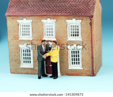 A real estate agent and a prospective buyer in front of a house on gold coin stilts, shaking hands on the deal, you are now the new owner of this glorious property.  - stock photo