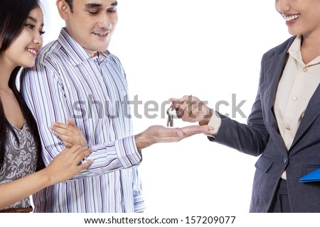A real estate agent giving a key of new house to her customer - stock photo