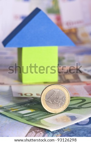 A real estate investment concept with one Euro coin and Euro banknotes and a toy house on the background - stock photo