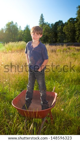 A real life young boy, with a faded shirt and dirty jeans, standing in a wheelbarrow in rural landscape. - stock photo