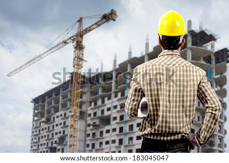 a rear view of architect with building construction site - stock photo