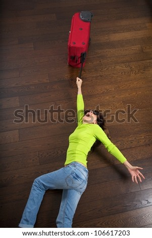 a rebel red suitcase drags a traveler woman - stock photo
