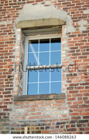 A reconstructed window in a red brick wall - stock photo