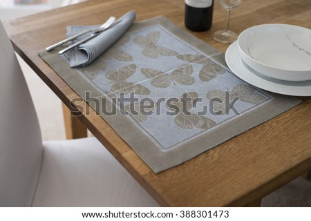 A rectangular placemat with embroidered butterflies as design spread out on wooden table with napkin and utensils atop alongside wine glass, a bottle of wine, and empty bowl on round dinner plate. - stock photo