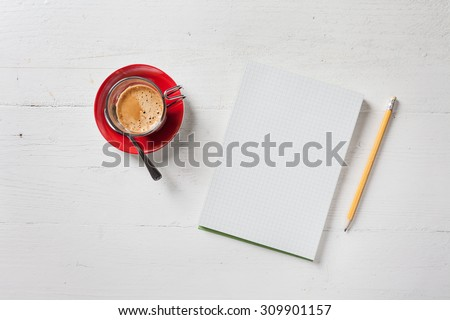 A recycled paper notebook checked with a black pencil with the eraser at the top and a cup of coffee with red saucer and spoon, are arranged on a wooden table painted white. View from the top - stock photo