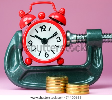 A red alarm clock placed in a Grey clamp against a pastel pink background, with a stack of gold coins in front of it, asking the question do you manage your time effectively? - stock photo
