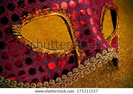 a red and golden carnival mask on a golden background - stock photo