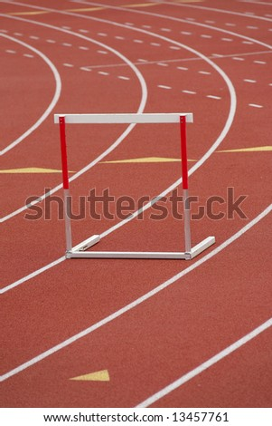 A red and white hurdle in a lane, on a synthetic track - stock photo