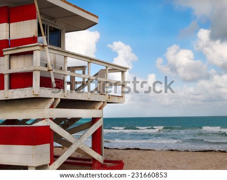 A red and white lifeguard shack in the sand facing the turquoise blue waters of the sea on a southern beach. - stock photo