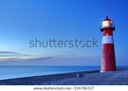 A red and white lighthouse at sea. Photographed at dusk near Westkapelle in Zeeland, The Netherlands. - stock photo