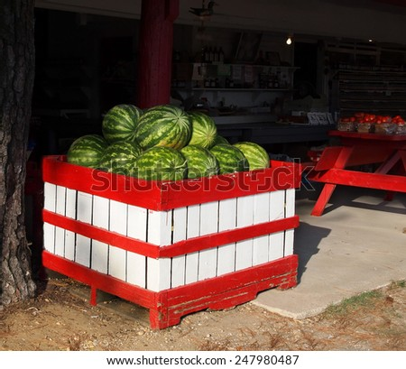 A red and white painted wooden bin full of ripe, green watermelons for sale at a country market. - stock photo