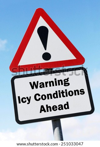 A red and white triangular road sign with a warning about icy conditions ahead concept against a partly cloudy sky. - stock photo