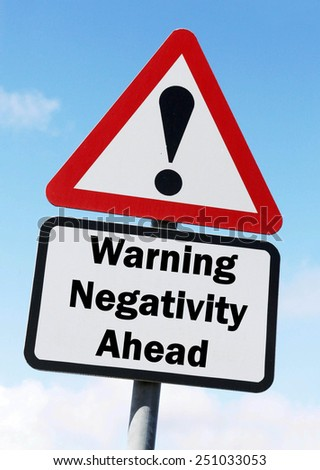 A red and white triangular road sign with a warning about negativity ahead concept against a partly cloudy sky. - stock photo