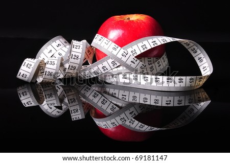a red apple surrounded by white tapeline - stock photo