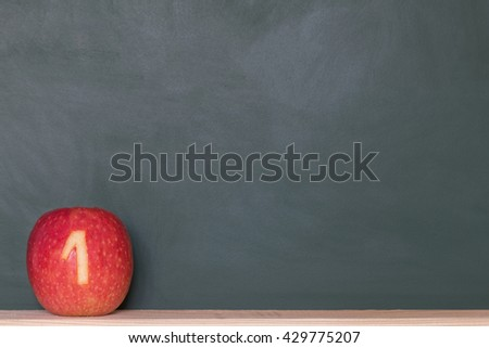 a red apple with a number in front of a blackboard - stock photo