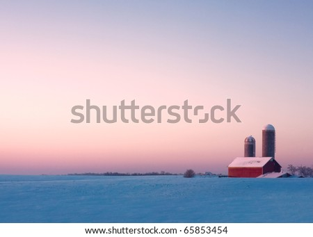 A red barn and silos surrounded by snow on an early winter morning. - stock photo
