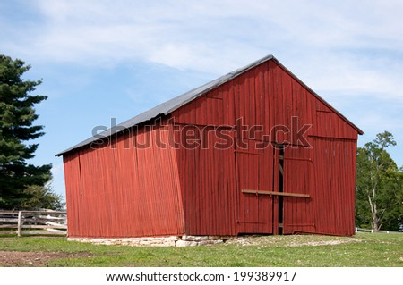 A red barn on a rock foundation. - stock photo