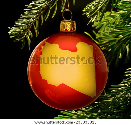 A red bauble with the golden shape of  Libya hanging on a christmas tree isolated on black.(series) - stock photo
